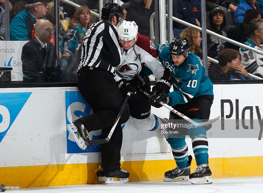 Andrew Desjardins #10 of the San Jose Sharks battles for the puck as it goes past the referee against Cody McLeod #55 of the Colorado Avalanche during an NHL game on December 23, 2013 at SAP Center in San Jose, California.