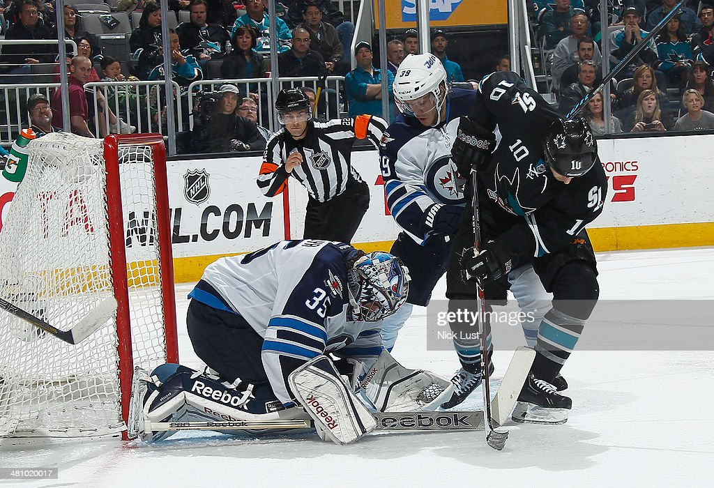 Andrew Desjardins #10 of the San Jose Sharks crashes the net against Al Montoya #35 andTobias Enstrom #39 of the Winnipeg Jets during an NHL game on March 27, 2014 at SAP Center in San Jose, California.