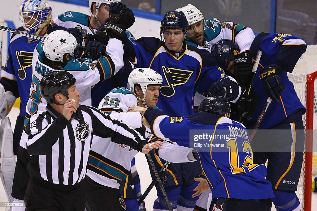 Andrew Desjardins of the San Jose Sharks tussles with Scott Nichol of the St Louis Blues at the Scottrade Center on March 12 2013 in St Louis Missouri