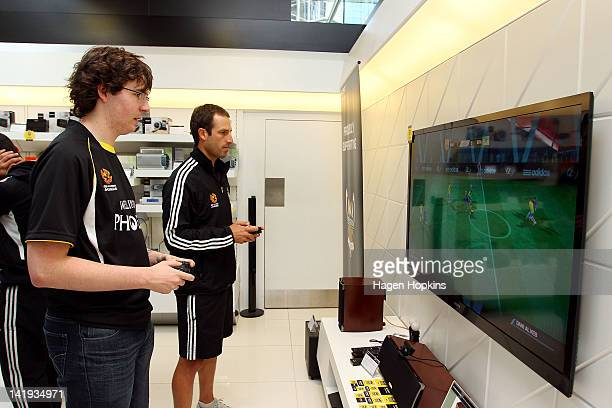 Andrew Durante plays a Playstation game with a Phoenix supporter during the Wellington Phoenix ALeague Finals Series launch at Sony Store on March 27...