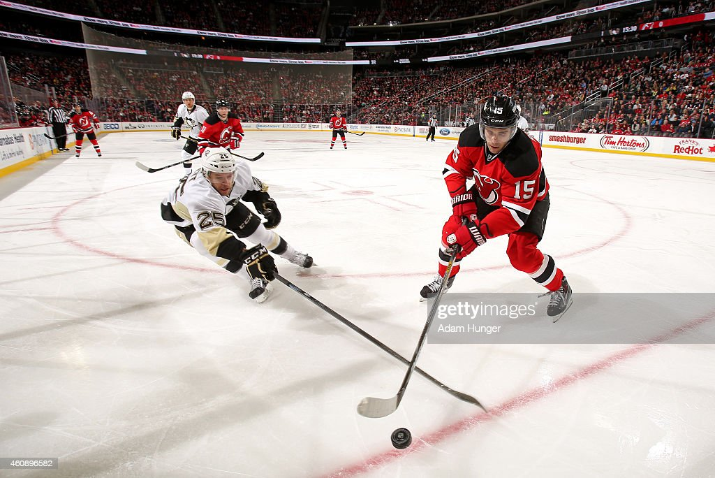 Andrew Ebbett of the Pittsburgh Penguins and Stefan Matteau of the New Jersey Devils battle for the puck during the second period at the Prudential...