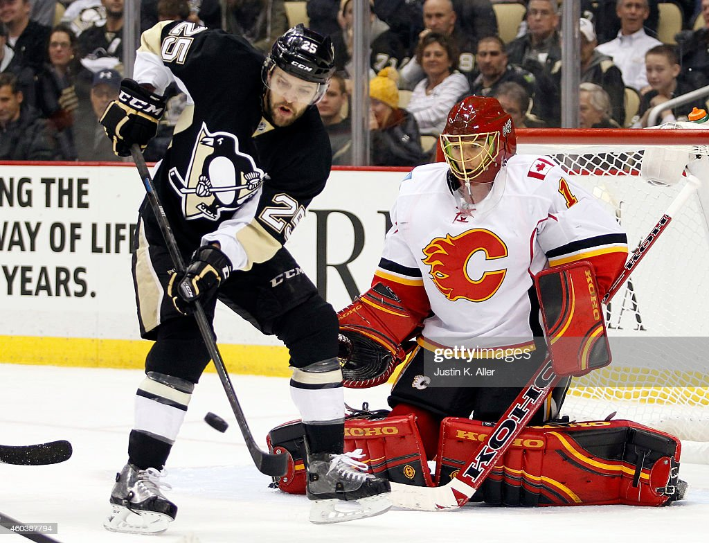 Andrew Ebbett of the Pittsburgh Penguins attempts to deflect a shot on Jonas Hiller of the Calgary Flames in the third period during the game at...