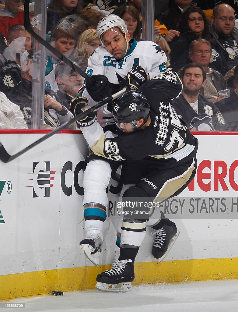 Andrew Ebbett of the Pittsburgh Penguins checks Dan Boyle of the San Jose Sharks into the boards during the first period on December 5 2013 at Consol...