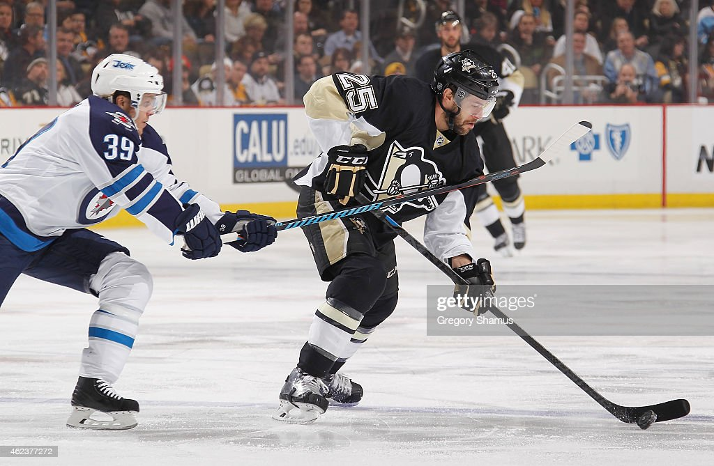 Andrew Ebbett of the Pittsburgh Penguins moves the puck in front of Tobias Enstrom of the Winnipeg Jets at Consol Energy Center on January 27 2015 in...