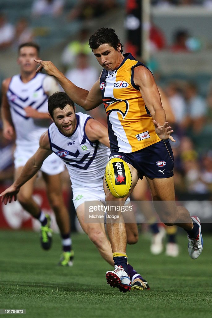Andrew Embley of the West Coast Eagles kicks the ball ahead of Hayden Ballantyne of the Fremantle Dockers during the round one NAB Cup match between the West Coast Eagles and the Fremantle Dockers at Patersons Stadium on February 16, 2013 in Perth, Australia.