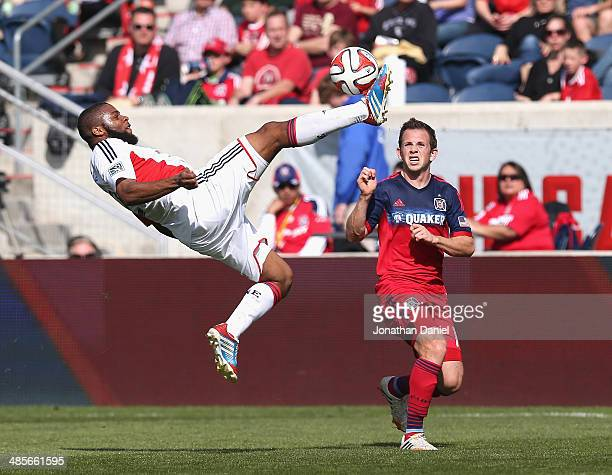 Andrew Farrell of the New England Revolution passes the ball with a bicycle kick next to Harry Shipp of the Chicago Fire during an MLS match at...