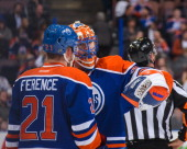 Andrew Ference and Ben Scrivens of the Edmonton Oilers confer between play against the San Jose Sharks during an NHL game at Rexall Place on March 25...