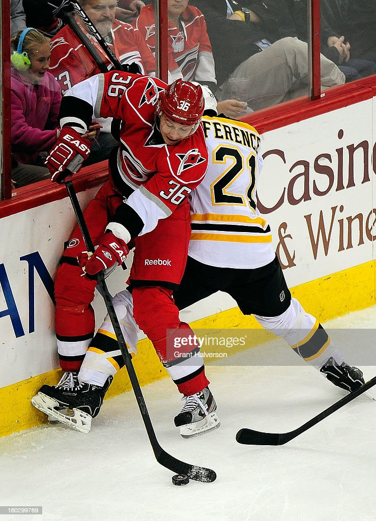 Andrew Ference #21 of the Boston Bruins battles for a puck along the boards with Jussi Jokinen #36 of the Carolina Hurricanes during play at PNC Arena on January 28, 2013 in Raleigh, North Carolina. The Bruins defeated the Hurricanes, 5-3.
