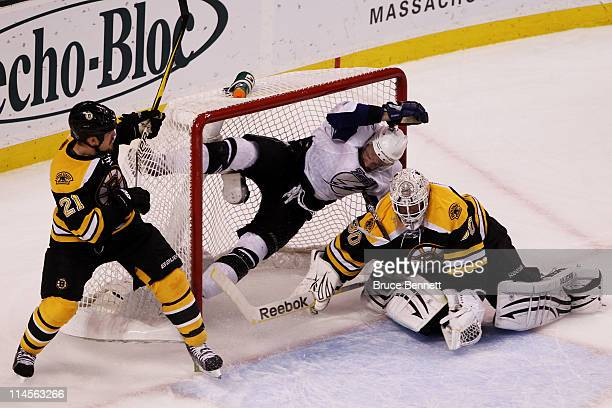 Andrew Ference of the Boston Bruins checks Steven Stamkos of the Tampa Bay Lightning over the top of Tim Thomas of the Boston Bruins and is called...