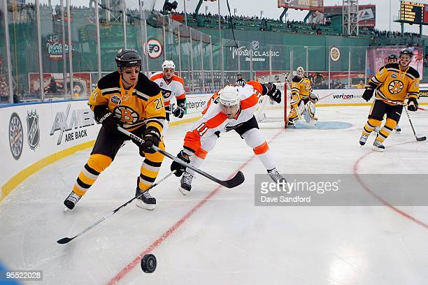 Andrew Ference of the Boston Bruins fights for the puck against Blair Betts of the Philadelphia Flyers during the 2010 Bridgestone NHL Winter Classic...