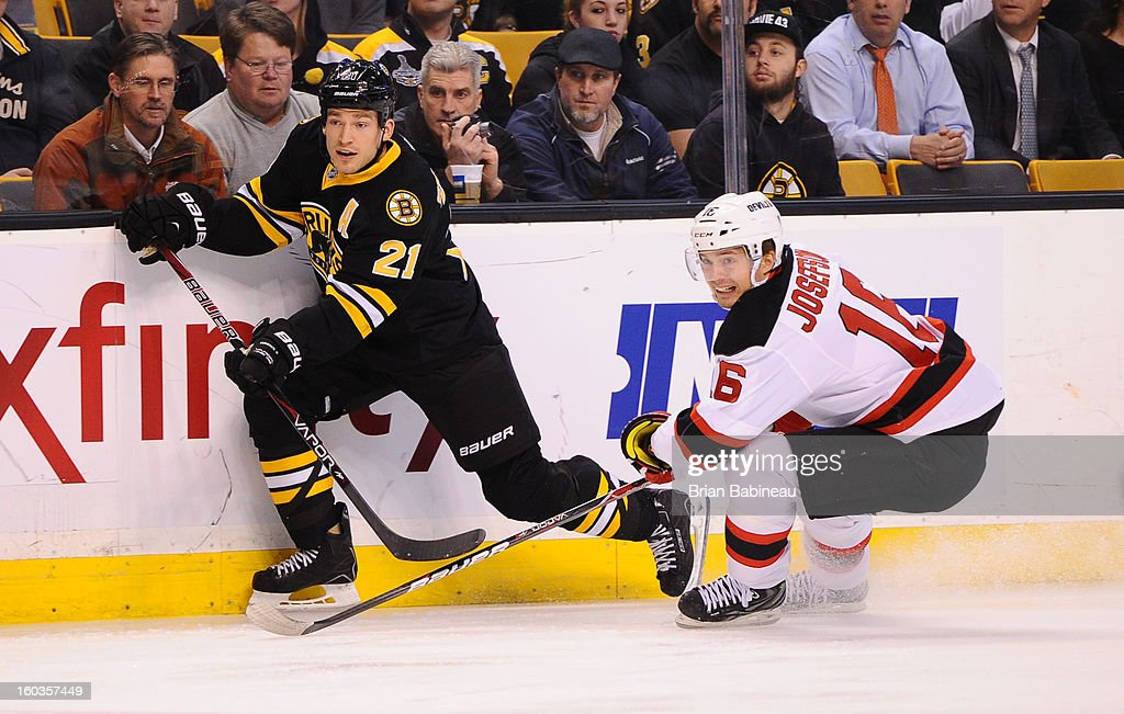 Andrew Ference #21 of the Boston Bruins passes the puck against Jacob Josefson #16 of the New Jersey Devils at the TD Garden on January 29, 2013 in Boston, Massachusetts.