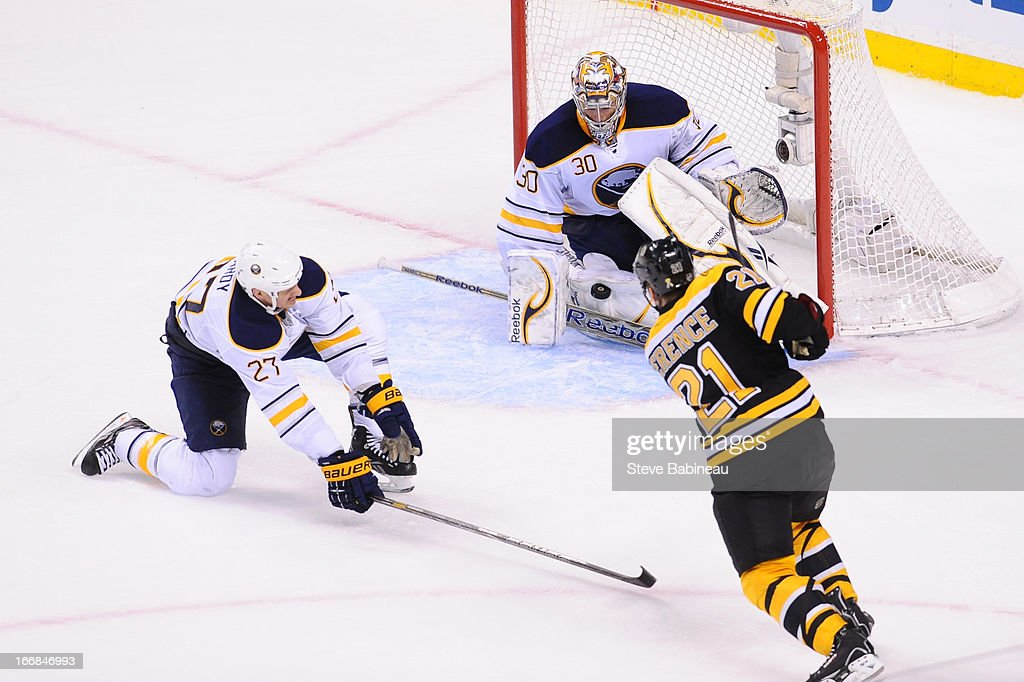 <a gi-track='captionPersonalityLinkClicked' href=/galleries/search?phrase=Andrew+Ference&family=editorial&specificpeople=202264 ng-click='$event.stopPropagation()'>Andrew Ference</a> #21 of the Boston Bruins shoots the puck against <a gi-track='captionPersonalityLinkClicked' href=/galleries/search?phrase=Adam+Pardy&family=editorial&specificpeople=2221762 ng-click='$event.stopPropagation()'>Adam Pardy</a> #27 and Ryan Miller #30 of the Buffalo Sabres at the TD Garden on April 17, 2013 in Boston, Massachusetts.