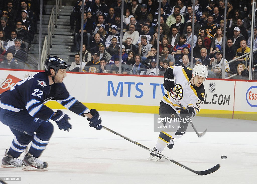 <a gi-track='captionPersonalityLinkClicked' href=/galleries/search?phrase=Andrew+Ference&family=editorial&specificpeople=202264 ng-click='$event.stopPropagation()'>Andrew Ference</a> #21 of the Boston Bruins shoots the puck down the ice as <a gi-track='captionPersonalityLinkClicked' href=/galleries/search?phrase=Chris+Thorburn&family=editorial&specificpeople=2222066 ng-click='$event.stopPropagation()'>Chris Thorburn</a> #22 of the Winnipeg Jets leans in with his stick to deflect it in third period action at the MTS Centre on December 6, 2011 in Winnipeg, Manitoba, Canada.