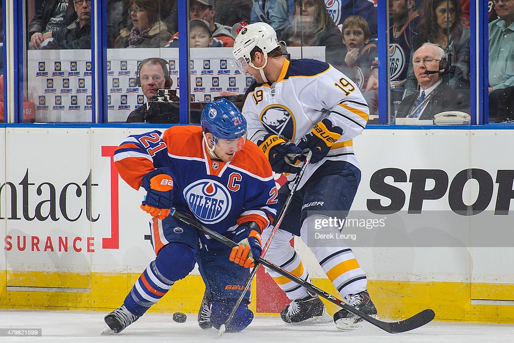 Andrew Ference #21 of the Edmonton Oilers battles for the puck against Cody Hodgson #19 of the Buffalo Sabres during an NHL game at Rexall Place on March 20, 2014 in Edmonton, Alberta, Canada.