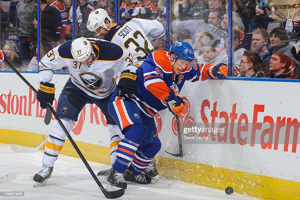 Andrew Ference #21 of the Edmonton Oilers battles for the puck against Matt Ellis #37 of the Buffalo Sabres during an NHL game at Rexall Place on March 20, 2014 in Edmonton, Alberta, Canada.