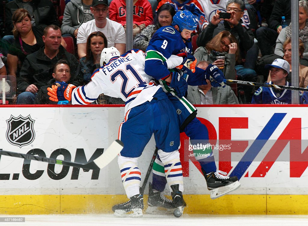 <a gi-track='captionPersonalityLinkClicked' href=/galleries/search?phrase=Andrew+Ference&family=editorial&specificpeople=202264 ng-click='$event.stopPropagation()'>Andrew Ference</a> #21 of the Edmonton Oilers checks <a gi-track='captionPersonalityLinkClicked' href=/galleries/search?phrase=Zack+Kassian&family=editorial&specificpeople=4604939 ng-click='$event.stopPropagation()'>Zack Kassian</a> #9 of the Vancouver Canucks into the boards during their NHL game at Rogers Arena October 11, 2014 in Vancouver, British Columbia, Canada. Vancouver won 5-4 in a shootout.