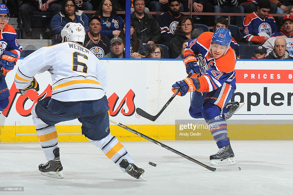 Andrew Ference #21 of the Edmonton Oilers takes a shot that is blocked by Mike Weber #6 of the Buffalo Sabres on March 20, 2014 at Rexall Place in Edmonton, Alberta, Canada.