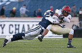 Andrew Fischer of the Harvard Crimson gains yards against the defense of Marquise Peggs of the Yale Bulldogs in the first half on November 21 2015 in...