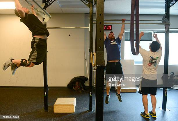 Andrew Fuller David Kaufman and Dan Tildert do pull ups during a crossfit session in the gym at Oracle Data Cloud on February 4 2016 in Westminster...