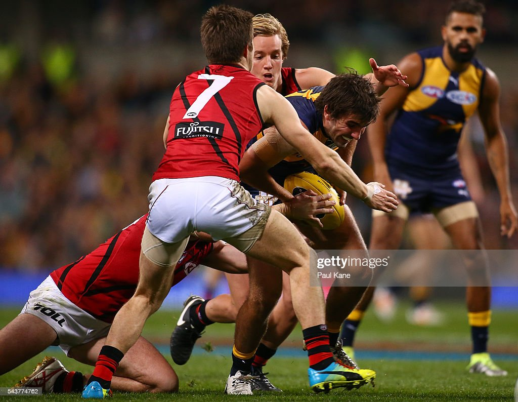 Andrew Gaff of the Eagles attempts to break from a tackle by Darcy Parish and Zach Merrett of the Bombers during the round 15 AFL match between the West Coast Eagles and the Essendon Bombers at Domain Stadium on June 30, 2016 in Perth, Australia.