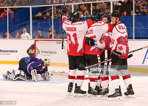 Andrew Gordon of Canada is congratulated by team mates after scoring a goal during the International Ice Hockey Invitational match between Canada and...