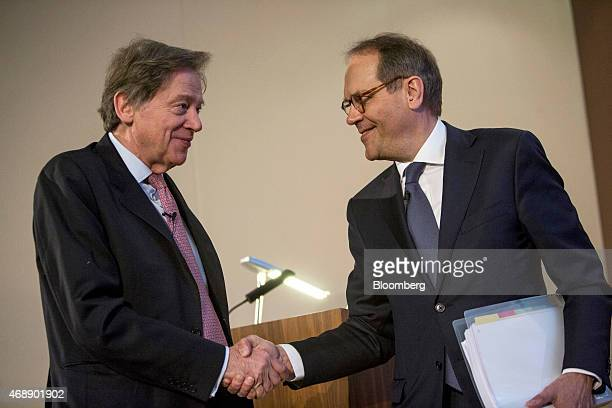 Andrew Gould chairman of BG Group Plc left shakes hands with Jorma Ollila chairman of Royal Dutch Shell Plc during a news conference at the London...