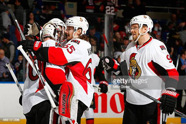 Andrew Hammond of the Ottawa Senators is congratulated by his teammates Milan Michalek and Erik Karlsson after defeating the New York Islanders at...