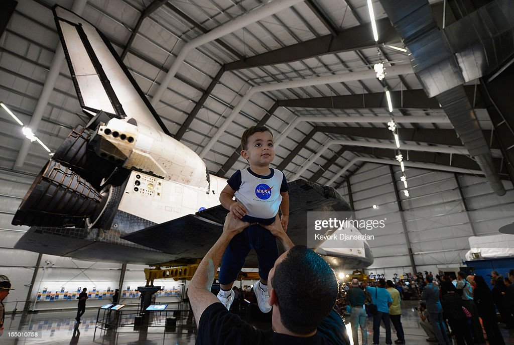 Andrew Hanna, who works for NASA, holds up his 17-month-old son Aaron during the space shuttle Endeavour exhibit grand opening ceremony at the new Samuel Oschin Pavilion of the California Science Center on October 30, 2012 in Los Angeles, California. The Orbiter arrived in Los Angeles in late September atop a modified Boeing 747. Then earlier this month nearly 1 million spectators looked on as Endeavour was transported on city streets during a three-day 11-mile journey from Los Angeles International Airport to the Science Center.