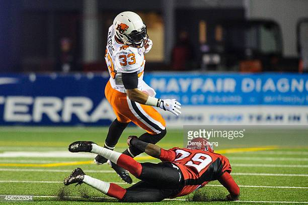 Andrew Harris of the BC Lions runs against Jamar Wall of the Calgary Stampeders during a CFL game at McMahon Stadium on September 27 2014 in Calgary...