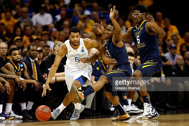 Andrew Harrison of the Kentucky Wildcats handles the ball against Juwan Staten and Devin Williams of the West Virginia Mountaineers in the first half...