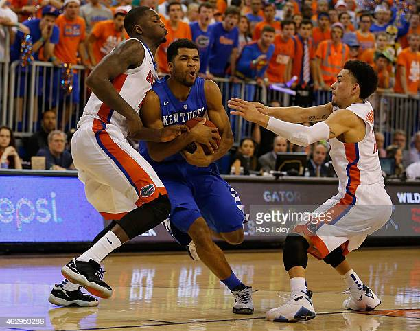 Andrew Harrison of the Kentucky Wildcats is defended by Dorian FinneySmith and Chris Chiozza of the Florida Gators during the second half of the game...