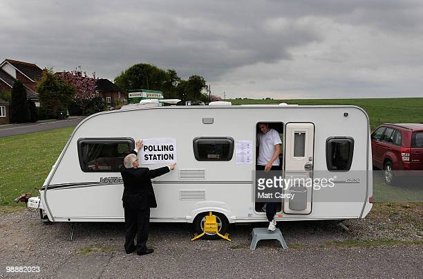 Andrew Hext presiding officer adjusts the polling station sign as a voter leaves the caravan being used as a polling station on May 6 2010 in Ford...