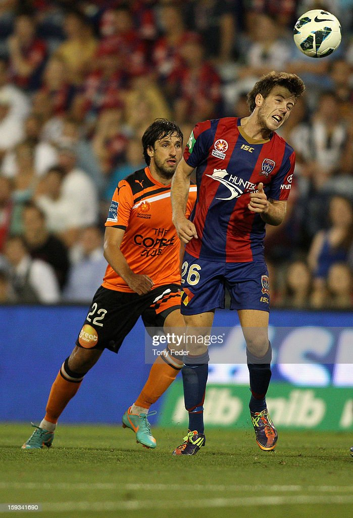 Andrew Hoole (R) of the Jets heads the ball in front of Thomas Broich of the Roar during the round 16 A-League match between the Newcastle Jets and the Brisbane Roar at Hunter Stadium on January 12, 2013 in Newcastle, Australia.