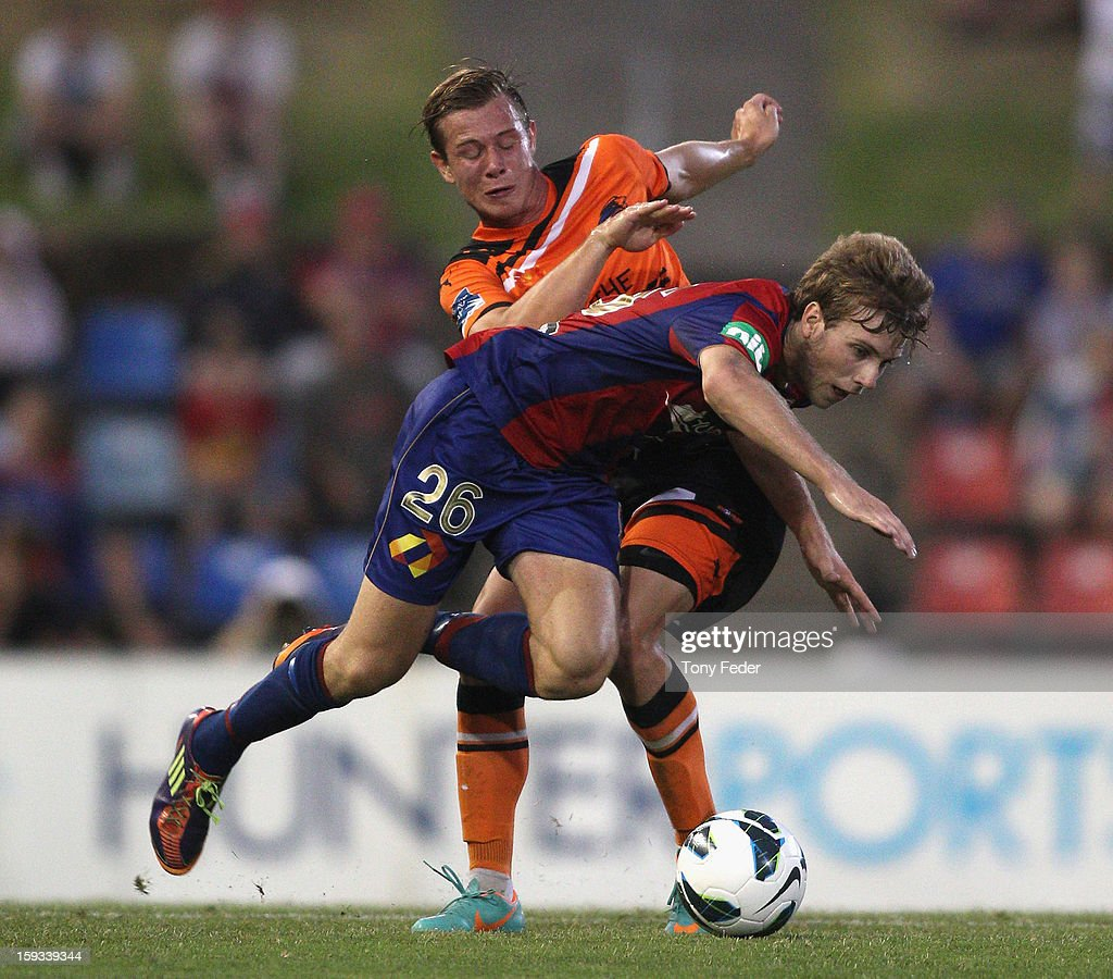 Andrew Hoole of the Jets is knocked off the ball by his Roar oponent during the round 16 A-League match between the Newcastle Jets and the Brisbane Roar at Hunter Stadium on January 12, 2013 in Newcastle, Australia.