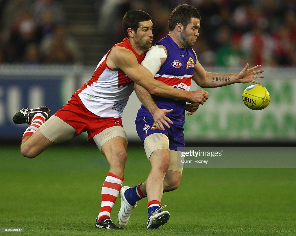 Andrew Hooper of the Bulldogs is tackled by Martin Mattner of the Swans during the AFL First Semi Final match between the Western Bulldogs and the Sydney Swans at Melbourne Cricket Ground on September 11, 2010 in Melbourne, Australia.