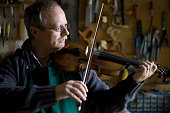 Andrew Hutchinson testing a violin and bow which he has just completed repairing and restoring at his workshop at Hoylake Wirral north west England...