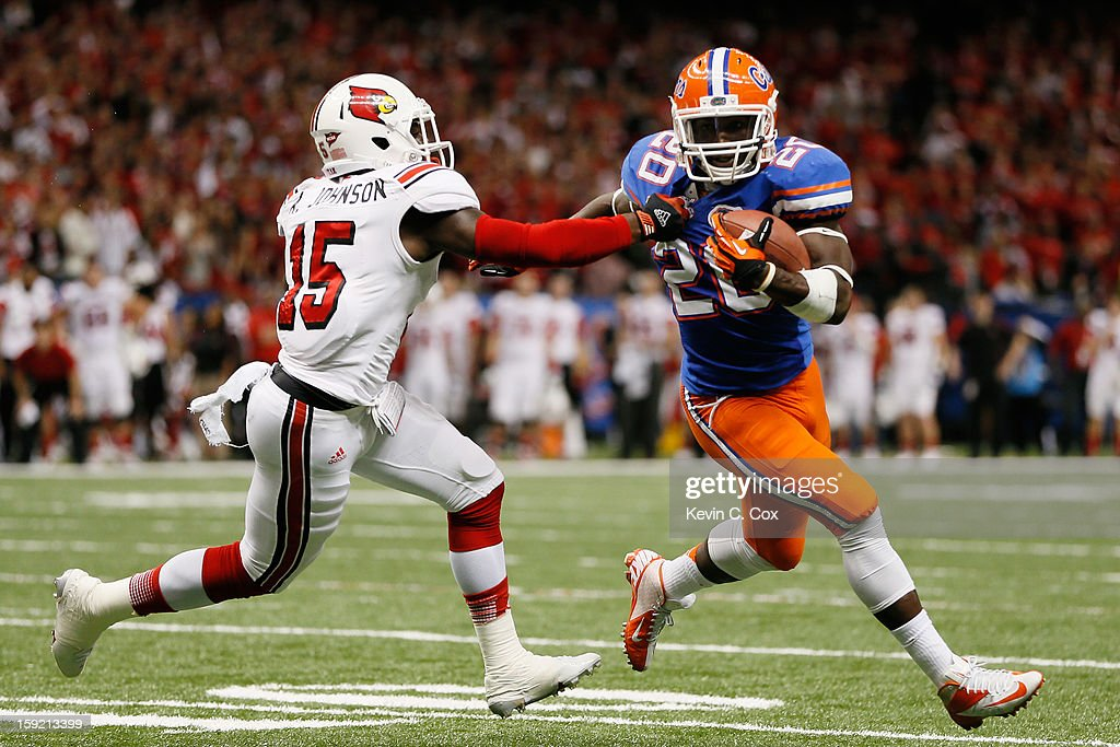 Andrew Johnson #15 of the Louisville Cardinals tackles Omarius Hines #20 of the Florida Gators during the Allstate Sugar Bowl at Mercedes-Benz Superdome on January 2, 2013 in New Orleans, Louisiana.