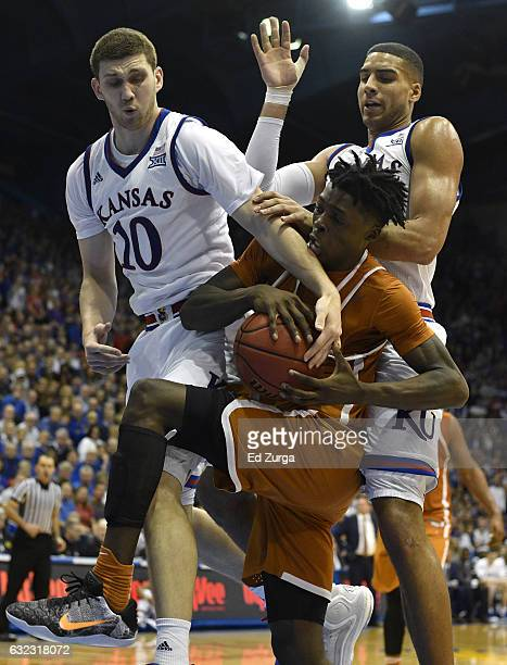 Andrew Jones of the Texas Longhorns rebounds the ball against Sviatoslav Mykhailiuk and Landen Lucas of the Kansas Jayhawks in the second half at...