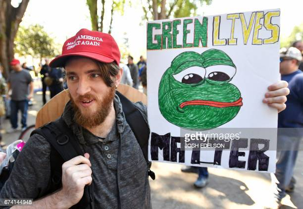 Andrew Knight holds a sign of Pepe the frog a conservative icon during a rally in Berkeley California on April 27 2017 Conservative firebrand Ann...