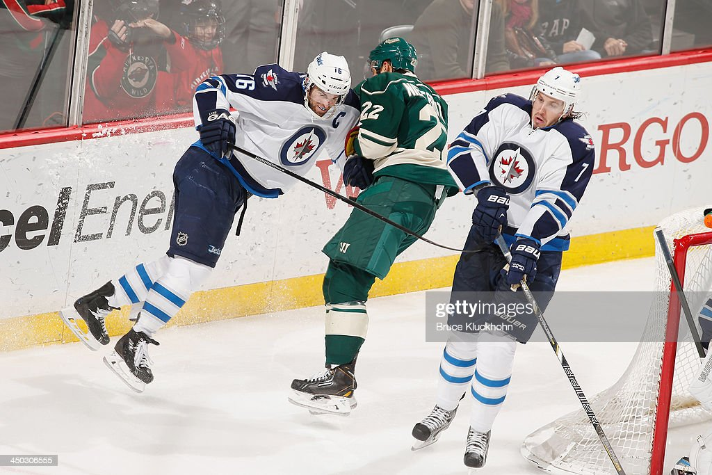 Andrew Ladd checks Nino Niederreiter of the Minnesota Wild as his Winnipeg Jets teammate Ian White avoids the collision during the game on November...