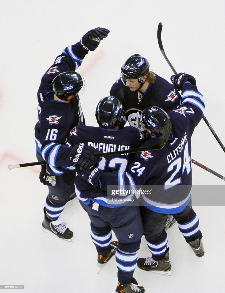 Andrew Ladd #16, Dustin Byfuglien #33, Grant Clitsome #24 and Bryan Little #18 of the Winnipeg Jets celebrate a third period goal against the New Jersey Devils at the MTS Centre on February 28, 2013 in Winnipeg, Manitoba, Canada.