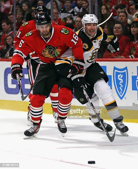 Andrew Ladd of the Chicago Blackhawks and Zdeno Chara of the Boston Bruins chase down the puck at the United Center on April 3 2016 in Chicago...