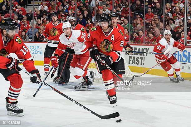 Andrew Ladd of the Chicago Blackhawks reaches for the puck in front of Duncan Keith as Tomas Jurco and Luke Glendening of the Detroit Red Wings watch...