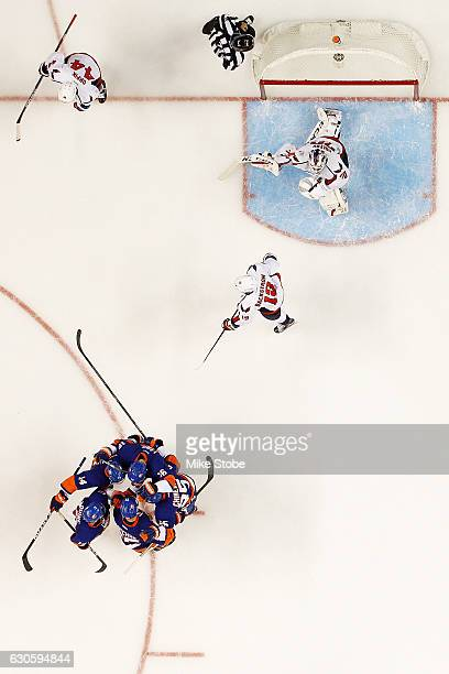 Andrew Ladd of the New York Islanders is mobbed by his teammates after scoring past Braden Holtby of the Washington Capitals at the Barclays Center...