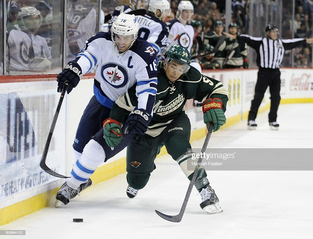Andrew Ladd of the Winnipeg Jets and Mathew Dumba of the Minnesota Wild battle for the puck during the second period of the game on October 10 2013...