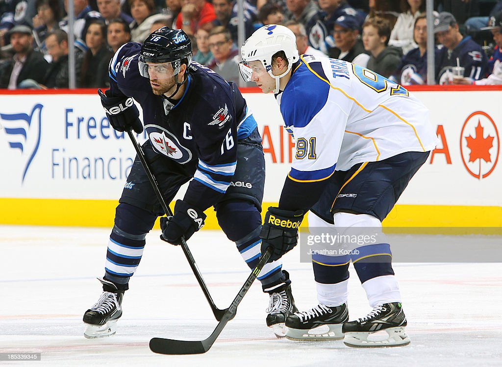 <a gi-track='captionPersonalityLinkClicked' href=/galleries/search?phrase=Andrew+Ladd&family=editorial&specificpeople=228452 ng-click='$event.stopPropagation()'>Andrew Ladd</a> #16 of the Winnipeg Jets and <a gi-track='captionPersonalityLinkClicked' href=/galleries/search?phrase=Vladimir+Tarasenko&family=editorial&specificpeople=6142635 ng-click='$event.stopPropagation()'>Vladimir Tarasenko</a> #91 of the St. Louis Blues get set for a third-period faceoff at the MTS Centre on October 18, 2013 in Winnipeg, Manitoba, Canada.