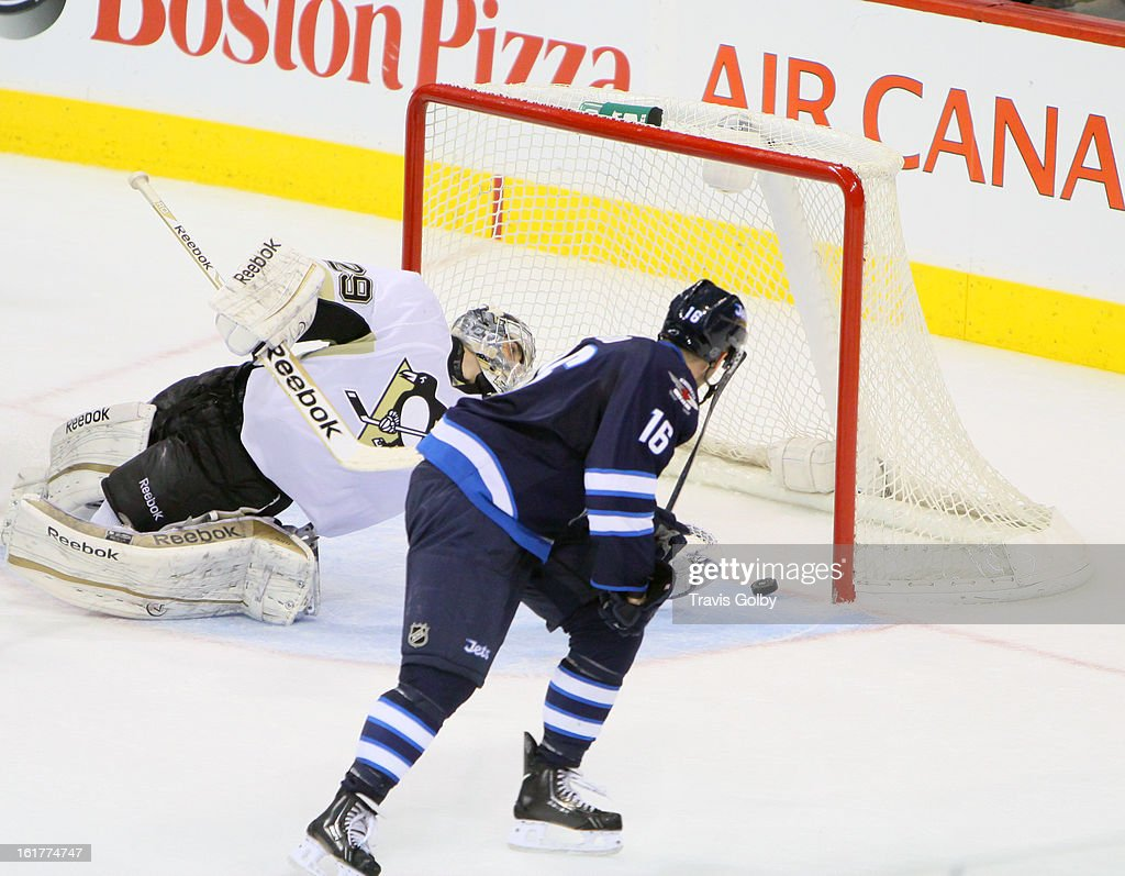 Andrew Ladd #16 of the Winnipeg Jets backhands the puck past a sprawling Marc-Andre Fleury #29 of the Pittsburgh Penguins for a late third period goal at the MTS Centre on February 15, 2013 in Winnipeg, Manitoba, Canada.