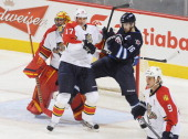 Andrew Ladd of the Winnipeg Jets battles for position against Filip Kuba of the Florida Panthers in front of goaltender Scott Clemmensen during...