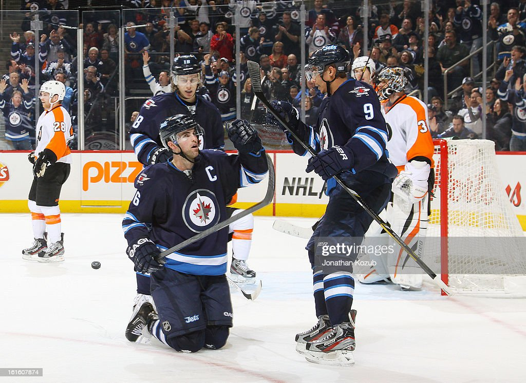 <a gi-track='captionPersonalityLinkClicked' href=/galleries/search?phrase=Andrew+Ladd&family=editorial&specificpeople=228452 ng-click='$event.stopPropagation()'>Andrew Ladd</a> #16 of the Winnipeg Jets celebrates a late third period goal against the Philadelphia Flyers from his knees as teammates <a gi-track='captionPersonalityLinkClicked' href=/galleries/search?phrase=Evander+Kane&family=editorial&specificpeople=4303789 ng-click='$event.stopPropagation()'>Evander Kane</a> #9 and <a gi-track='captionPersonalityLinkClicked' href=/galleries/search?phrase=Bryan+Little&family=editorial&specificpeople=540533 ng-click='$event.stopPropagation()'>Bryan Little</a> #18 join him at the MTS Centre on February 12, 2013 in Winnipeg, Manitoba, Canada.