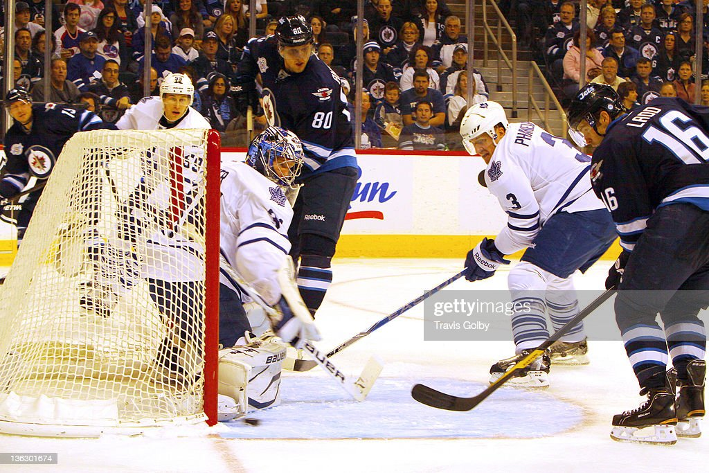 <a gi-track='captionPersonalityLinkClicked' href=/galleries/search?phrase=Andrew+Ladd&family=editorial&specificpeople=228452 ng-click='$event.stopPropagation()'>Andrew Ladd</a> #16 of the Winnipeg Jets deflects the puck into the net as goaltender James Reimer #34 of the Toronto Maple Leafs tries to make the stop during second period action at the MTS Centre on December 31, 2011 in Winnipeg, Manitoba, Canada.